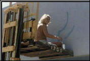 A Clenet staff member shows her artistic bent by painting the logo on the new Factory 3 in Carpinteria.
